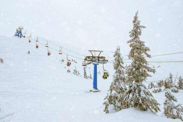 Kolejki linowe wiszą na kablach w cichym nocnym ośrodku narciarskim na tle oszałamiającego gwiaździstego nieba w pogodną zimową noc