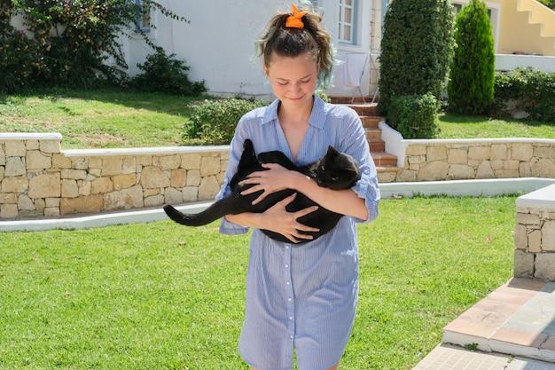 Kolejna dziewczyna nastolatka trzymając piękny czarny kot w ramionach, słoneczny letni dzień