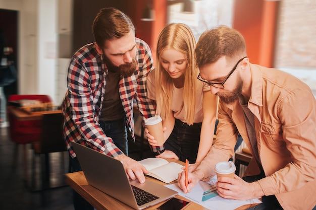 Kolejne zdjęcie trzech partnerów biznesowych pracujących nad projektem. mają spotkanie w kawiarni. chłopaki i dziewczyna studiują grafikę i zapisują informacje na ten temat.