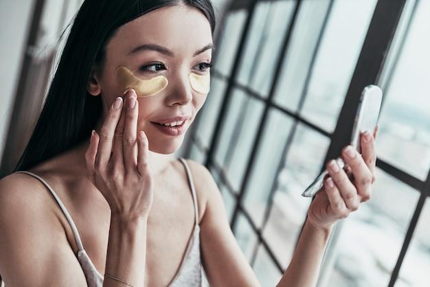 Kolejny zabieg. atrakcyjna młoda kobieta używająca opasek na oczy i uśmiechająca się podczas spędzania czasu w domu