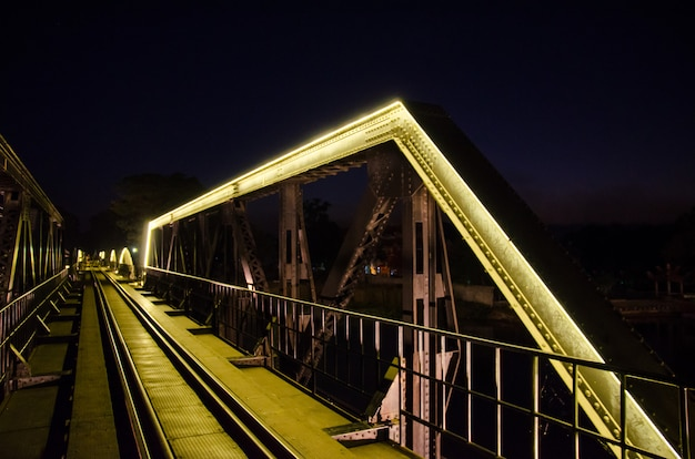 Kolejowy most z żółtą neonową lampą przy kanchanaburi, tajlandia z selekcyjną ostrością