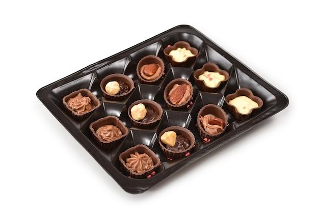 Kolekcja cukierków czekoladowych w plastikowym pudełku.