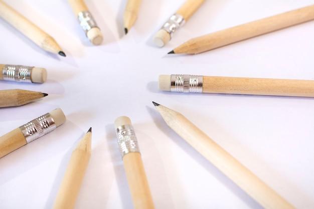 Kolekcja drewnianych ołówków umieszczonych w okręgu, niektóre spiczaste, a inne przy gumce.