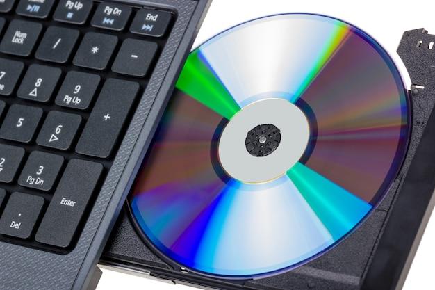 Kolekcja elektroniczna - laptop z otwartą tacą dvd na białym tle