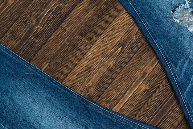 Kolekcja jeansów postrzępionych lub jeansów niebieskich na szorstkim ciemnym drewnie