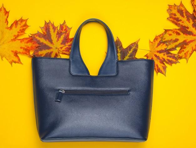 Kolekcja jesienna. skórzana torba z opadłych liści jesienią na żółto. akcesoria sezonowe. widok z góry. skopiuj miejsce