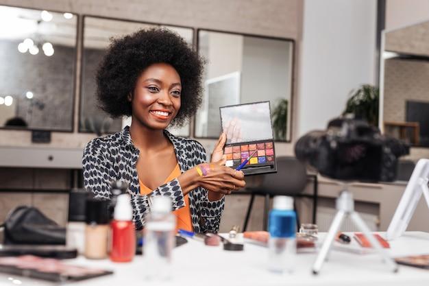 Kolekcja kolorów. niesamowita kobieta z kręconymi włosami uśmiecha się opowiadając o nowej kolekcji kolorów