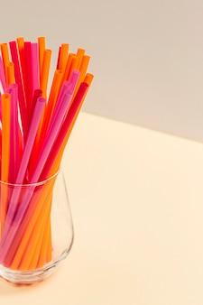 Kolekcja kolorowych plastikowych słomek w szkle