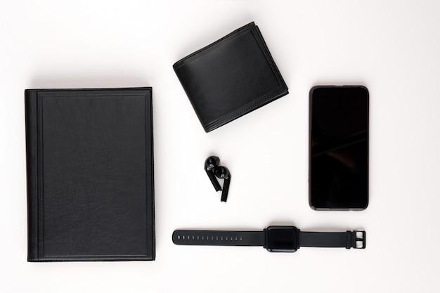 Kolekcja męska. czarny skórzany pamiętnik, czarny długopis, zegarek, telefon i słuchawki na białym tle. widok z góry.