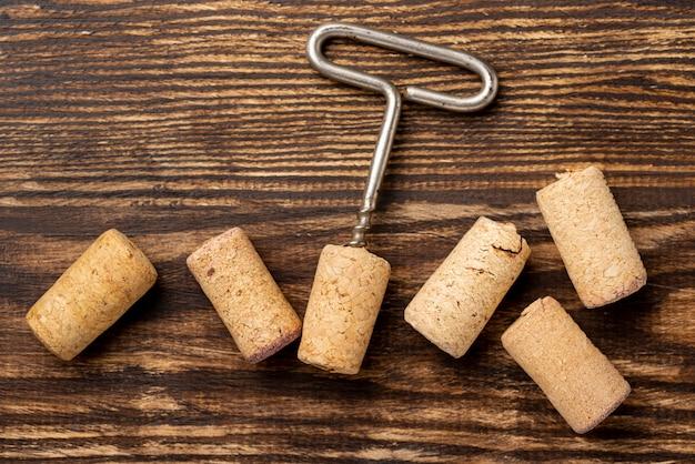 Kolekcja płaskich korków do wina obok korkociągu