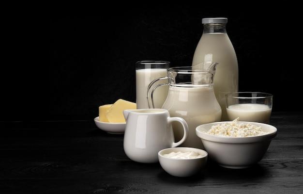 Kolekcja produktów mlecznych na czarnym tle drewnianych z miejsca na kopię
