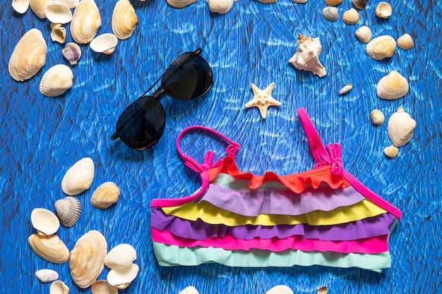Kolekcja przedmiotów podróżnych, w tym walizka, okulary przeciwsłoneczne, kostium kąpielowy, krem do opalania i muszle na turkusowym granatowym tle
