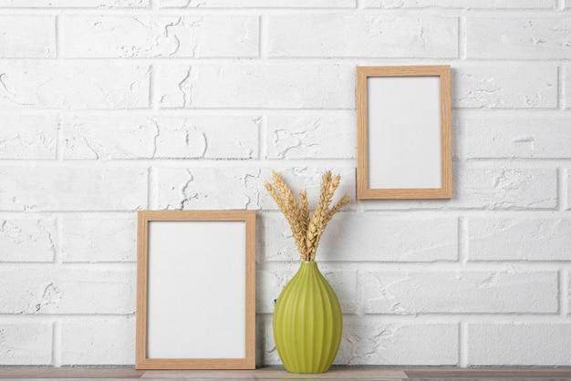 Kolekcja pustych ramek na ścianie i obok wazonu