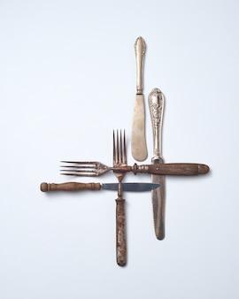 Kolekcja starego metalu z drewnianą rączką widelców i noży na szarym tle z miejsca na kopię. kolekcja vintage. leżał na płasko