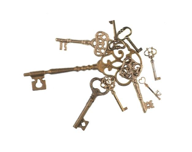 Kolekcja starożytnych złotych kluczy na białym tle