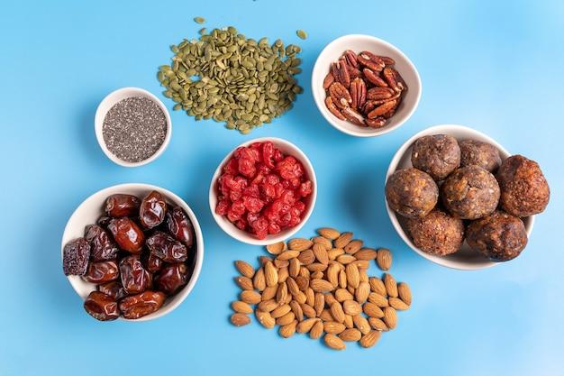 Kolekcja superfoods i orzechów w miseczkach dla zdrowia, sprawności i witalności wykorzystywana do przygotowywania kulek energetycznych. widok z góry. na niebieskim tle.