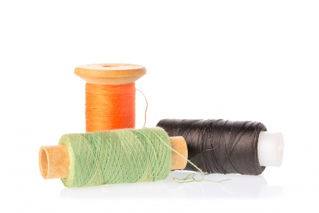 Kolekcja szpul nici koloru na białym tle.