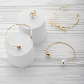 Kolekcja trzech bransoletek i pierścionka na białych platformach na drewnianym z miejsca kopiowania