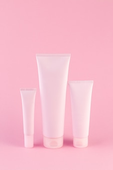 Kolekcja trzech tubek kosmetycznych na pastelowym różowym tle.