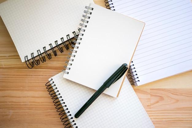 Kolekcja zeszytów i czarny długopis do pisania