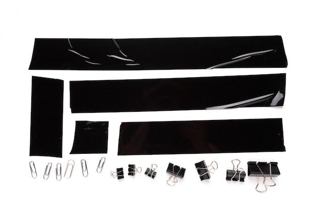 Kolekcja zużytych kawałków czarnej taśmy elektrycznej z przyborami biurowymi