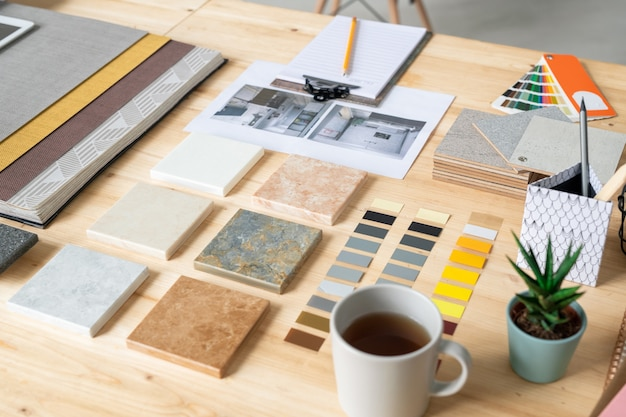 Kolekcje płytek marmurowych, tapety, próbki kolorów, zdjęcia wnętrza domu, filiżanka herbaty, komplet papierów