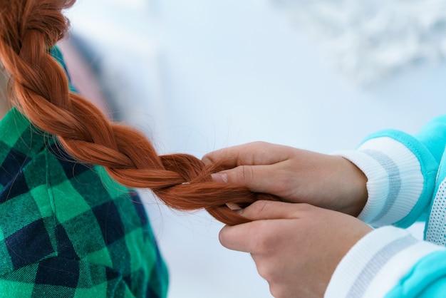 Koleżanka zaplata warkocz rudowłosej dziewczynie