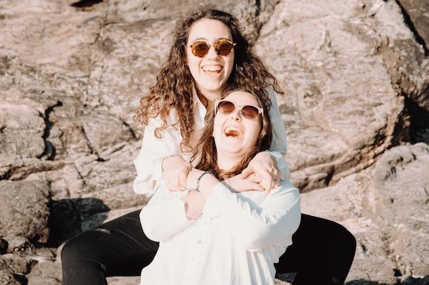 Koleżanki bawią się w dzień, na plaży i śmieją się w letni dzień.