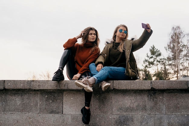 Koleżanki, biorąc selfie razem na zewnątrz