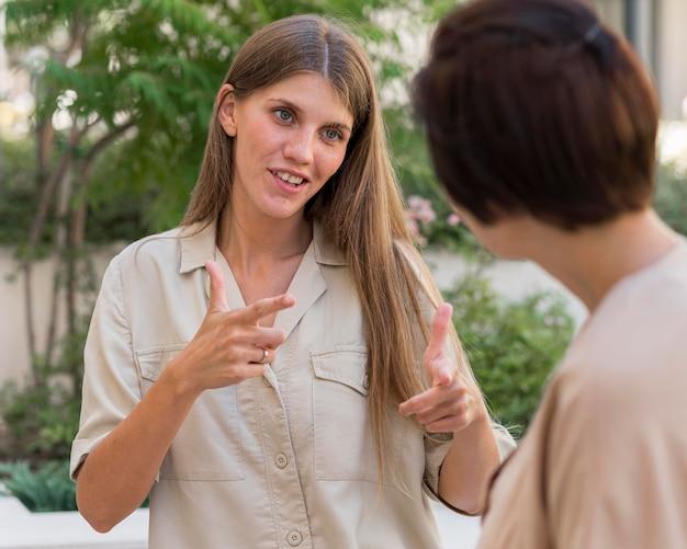 Koleżanki komunikujące się na zewnątrz za pomocą języka migowego