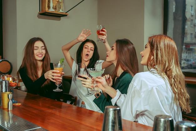 Koleżanki o drinki w barze. siedzą przy drewnianym stole z koktajlami. brzęczą szklankami