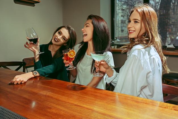 Koleżanki o drinki w barze. siedzą przy drewnianym stole z koktajlami. brzęczą szklanki