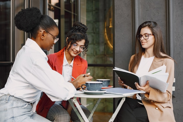 Koleżanki omawiając dane w kawiarni na świeżym powietrzu. wielorasowe kobiety analizujące strategię produkcyjną projektowania biznesowego z wykorzystaniem dokumentów w kawiarni ulicznej