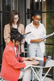 Koleżanki Omawiając Dane W Kawiarni Na świeżym Powietrzu. Wielorasowe Kobiety Analizujące Strategię Produkcyjną Projektowania Biznesowego Z Wykorzystaniem Dokumentów W Kawiarni Ulicznej Premium Zdjęcia
