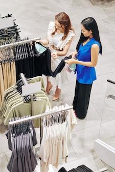 Koleżanki patrząc na czarną bluzkę na stojaku w sklepie, widok z góry