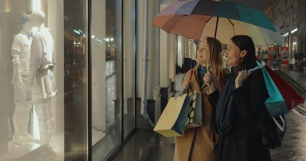 Koleżanki przed sklepami pokazują okno