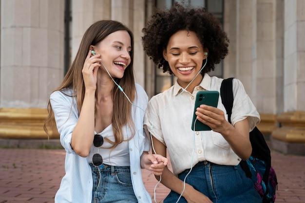 Koleżanki słuchają muzyki na słuchawkach ze smartfona na zewnątrz