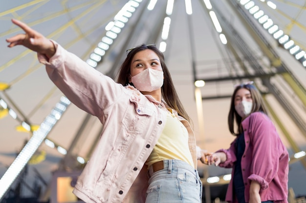Koleżanki w parku rozrywki z maskami medycznymi