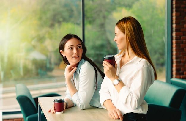 Koleżanki z kaukaskiej grupy etnicznej spotykają się, cieszą się przyjazną i ciepłą rozmową. współpracownicy prowadzący nieformalną rozmowę, pijący kawę na przerwach od pracy.