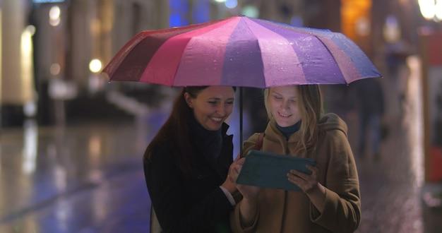 Koleżanki z tabletem pod parasolem