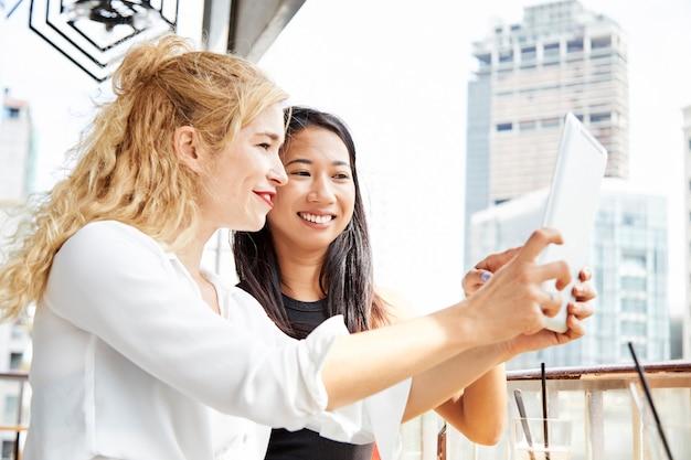 Koleżanki za pomocą aplikacji na cyfrowym tablecie