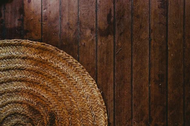 Kółkowa łozinowa mata na drewnianym podłogowym tle, widok od above.