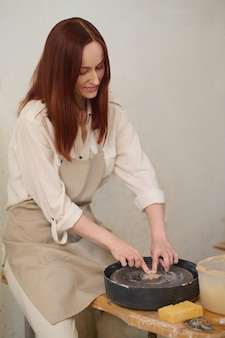 Koło garncarskie. kobieta garncarka pracująca na kole garncarskim w warsztacie