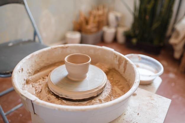 Koło garncarskie z glinianym garnkiem, nikt, wnętrze warsztatu. ręcznie robione formowanie i kształtowanie zastawy stołowej