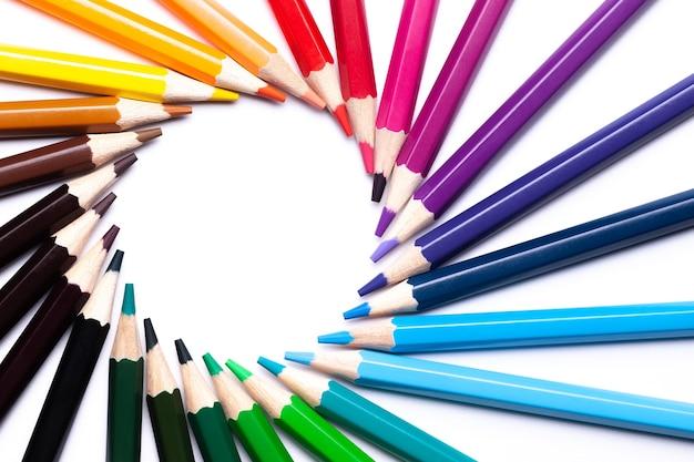 Koło lub tęczowy wir kolorowych ołówków na białym tle po lewej stronie, kopia spacja, makieta, symbol lgbt.