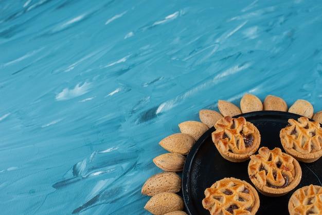 Koło migdałów w łupinach z słodkie świeże okrągłe ciasteczka na niebieskim tle.