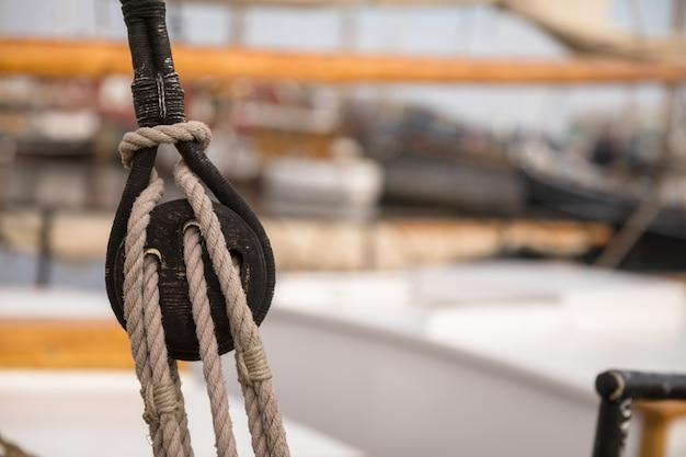 Koło pasowe do żagli i lin wykonanych z drewna na starej żaglówce, z nieostrym żaglem i innymi łodziami