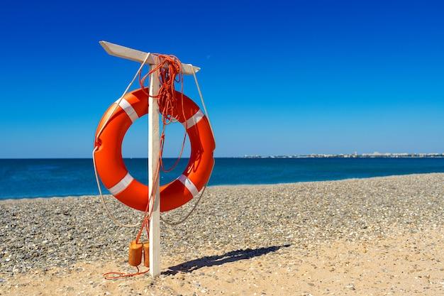 Koło ratunkowe na plaży z morzem