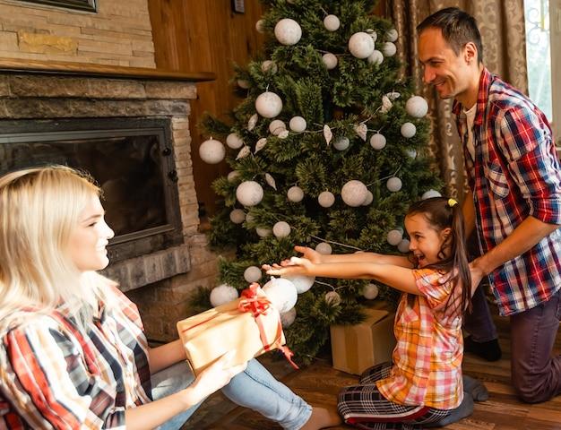 Koło rodziny tematu bożego narodzenia i nowego roku. młoda rodzina kaukaski siedzi na drewnianej podłodze domu w salonie przy kominku choinka.