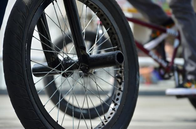 Koło rowerowe bmx na tle niewyraźnej ulicy z rowerzystami. pojęcie sportów ekstremalnych